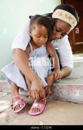 Mother helping her daughter put her sandals on. Cape Town, South Africa - Stock Image