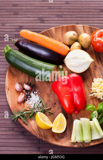 Ingredients vegetables for soup with pesto sauce and basil on a wooden plate. - Stock Image