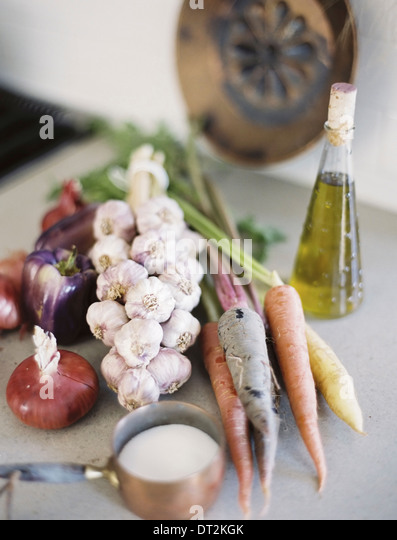 A tabletop A group of fresh organic vegetables carrots and onions garlic and peppers A flask of oil and a copper - Stock Image