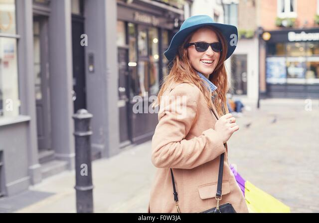 Portrait of stylish young woman looking over her shoulder, London, UK - Stock Image