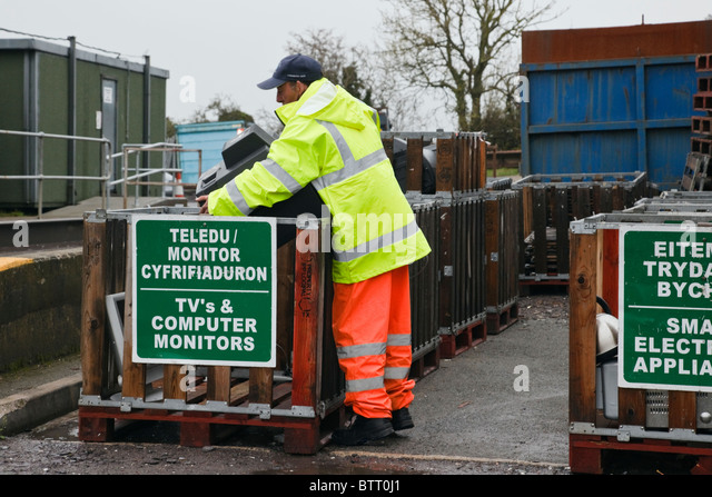Workman disposing of an old TV in container at Council refuse site for household waste. UK Britain - Stock Image