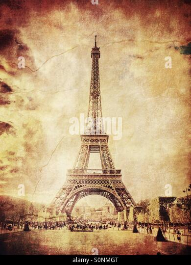 View of Eiffel Tower from Champs de Mars in Paris, France. Aged sepia tones and vintage paper texture overlay. - Stock Image