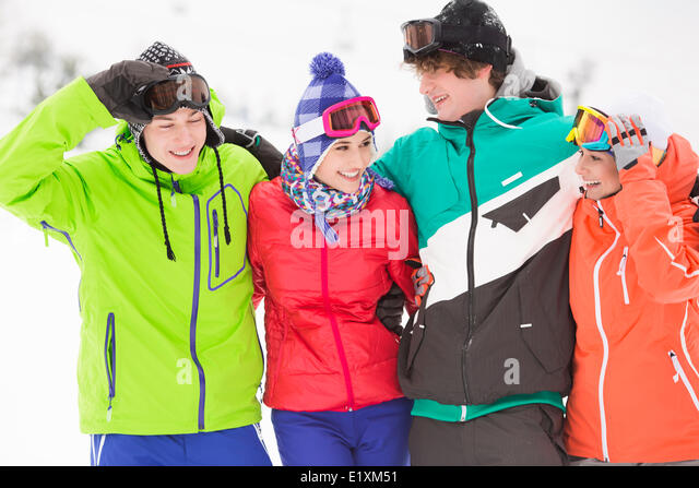 Portrait of young friends in warm clothing outdoors - Stock Image
