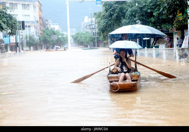 Liuzhou, China's Guangxi Zhuang Autonomous Region. 14th Aug, 2017. Local residents row on a flooded street in - Stock Image