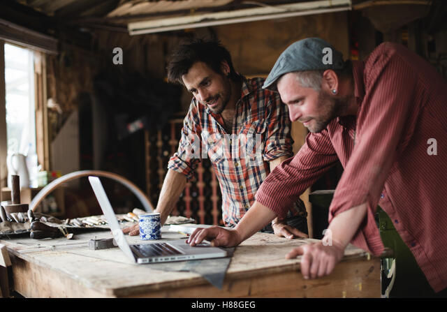 Two carpenters checking their design on a laptop - Stock-Bilder