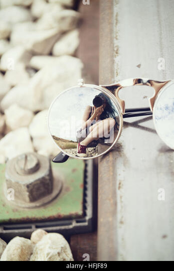 Young woman reflected on a sunglasses - Stock Image