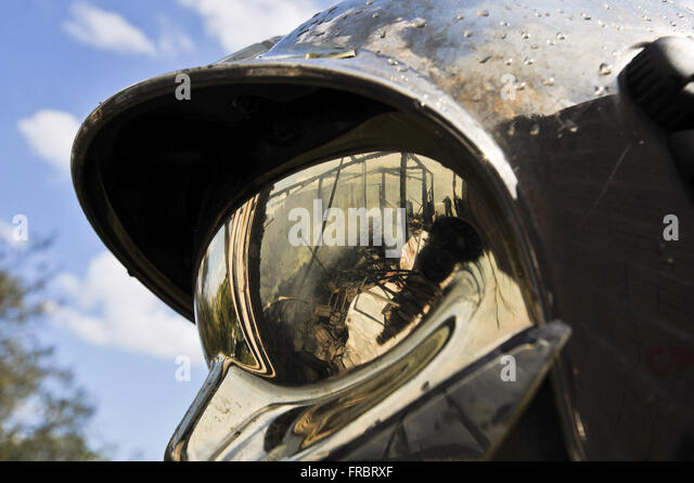 Detail of reflection of the wreckage of house burning in fireman`s helmet - Stock Image