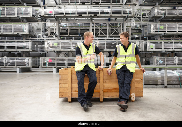 Two warehouse workers leaning on crate in engineering warehouse - Stock Image