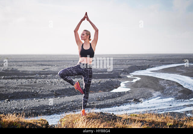 Young women practising yoga by a deserted unmade road in Southern Iceland - Stock Image