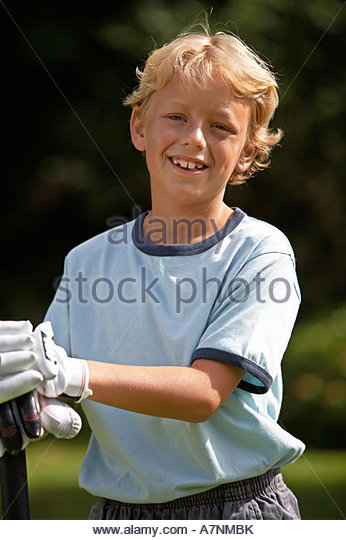 Blonde boy 8 10 playing cricket in garden wearing cricket gloves smiling close up portrait - Stock Image