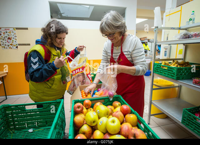 Mainz, Germany. 28th Apr, 2016. Volunteer Erika Schwalbach (R) puts easter eggs in the shopping bag of single mother - Stock Image