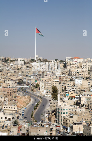 The city of Amman with the Jordanian flag flying; Jordan - Stock Image