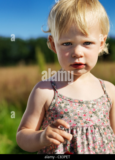 Toddler girl standing outdoors - Stock Image