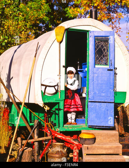 Portrait of basque girl in traditional clothing standing in the doorway of Sheephearders Wagon, Boise, Idaho, USA - Stock Image
