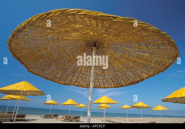 Turkey Aegean Coast Pamucak Beach beach yellow wicker umbrellas for rent - Stock Image