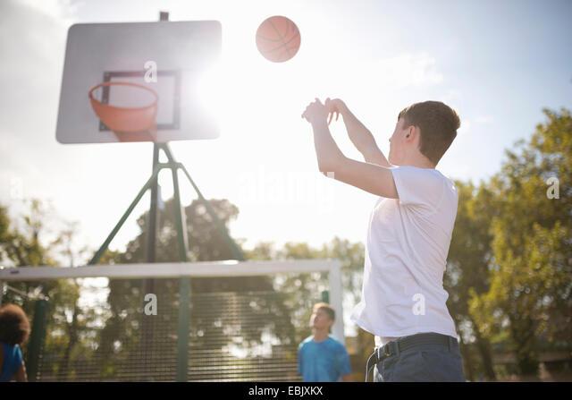Young male basketball player throwing basketball into hoop - Stock Image