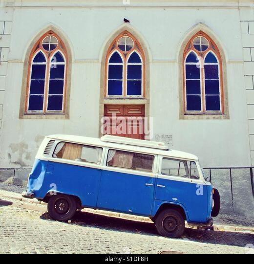 A vintage Volkswagen camper van parked in a sloping street in Lisbon, Portugal - Stock-Bilder