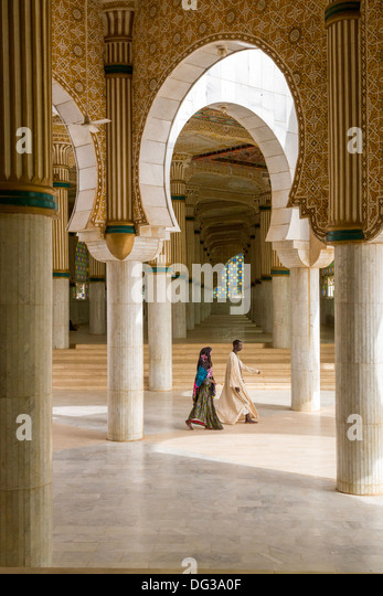 Senegal, Touba. Prayer Halls for Overflow Crowds at the Grand Mosque. Man and Woman Walking. - Stock Image