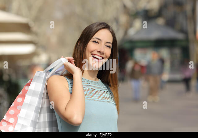 Happy consumer woman buying and holding shopping bags in the street of a city - Stock Image