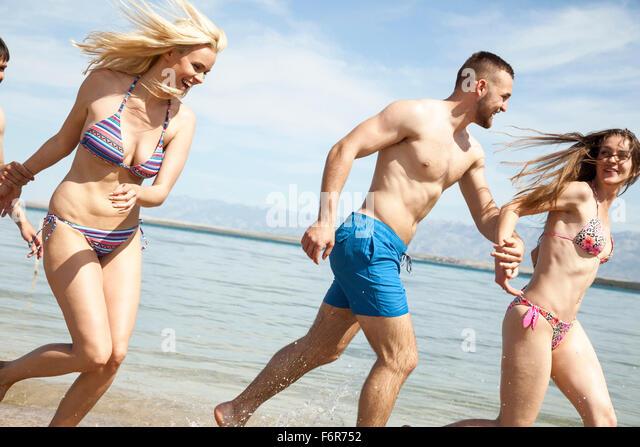 Group of friends on beach having fun - Stock Image