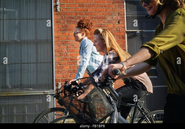 Side view of women cycling on bicycles past warehouse - Stock-Bilder