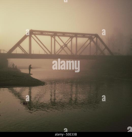 Fisherman in fog under bridge - Stock Image