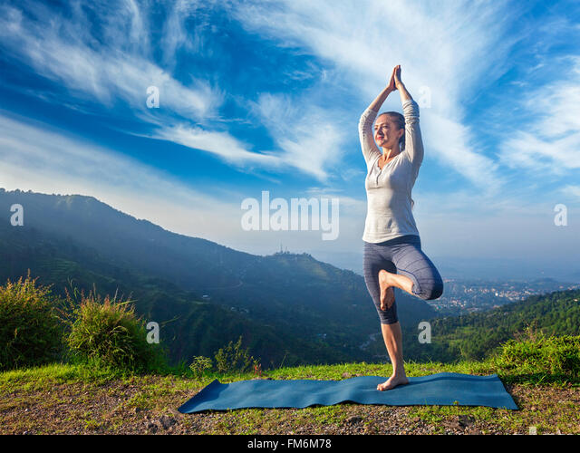 Woman in yoga Vrikshasana tree pose outdoors - Stock-Bilder