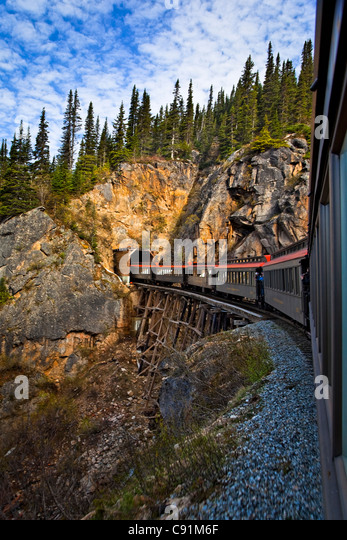 White Pass & Yukon train crosses a trestle and enters a tunnel, Skagway, Southeast Alaska, Summer - Stock Image