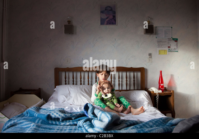 Little boy sitting with his baby sister on hotel bed - Stock-Bilder