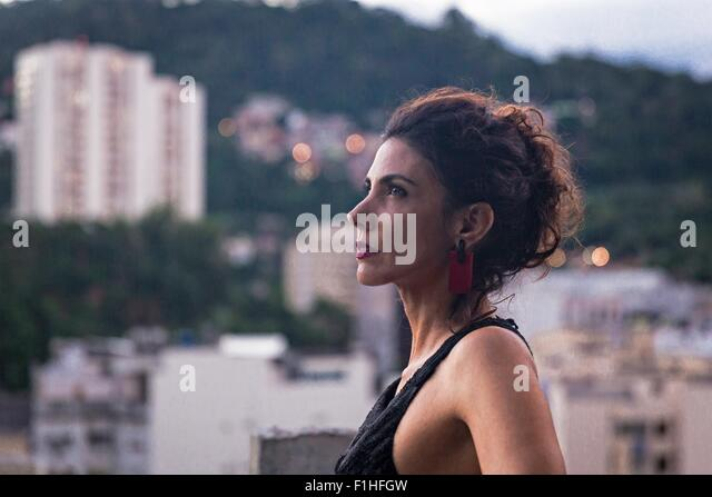 Profile portrait of fashion model wearing black dress and looking up - Stock Image