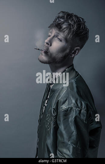 Studio portrait of a bearded young man smoking a cigarette. - Stock Image