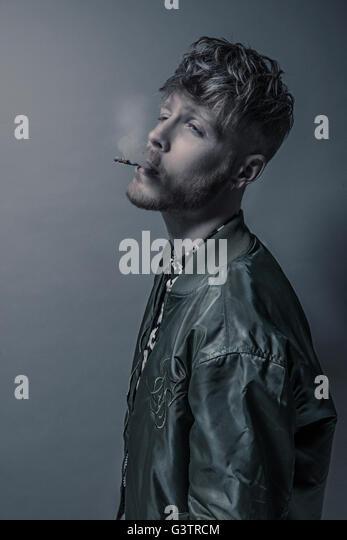 Studio portrait of a bearded young man smoking a cigarette. - Stock-Bilder