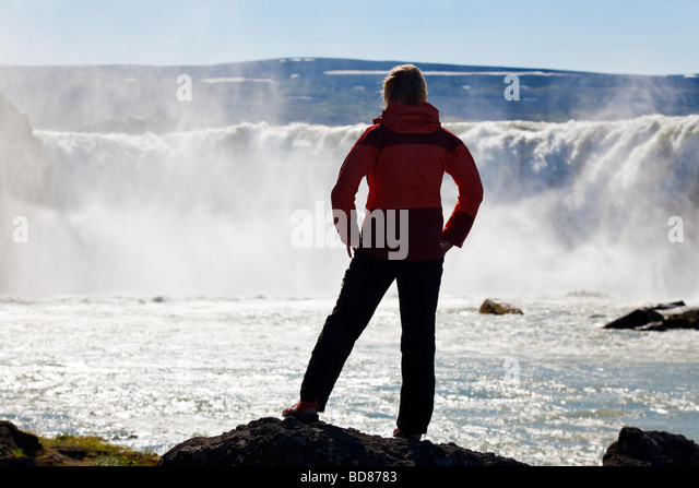 A woman hiker standing in front of a huge waterfall Shot on location at Godafoss waterfall in Iceland - Stock Image