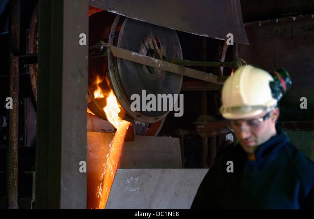 Steel worker in front of running molten metal in steel foundry - Stock Image