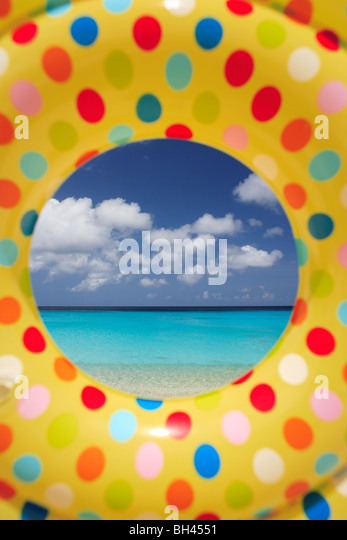 A tropical beach viewed through the hole in a brightly colored inflatable rubber ring (vertical) - Stock Image