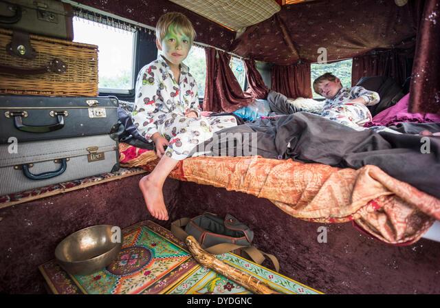 Two boys having fun in a VW camper van  at a festival. - Stock-Bilder