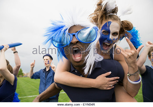 Portrait enthusiastic fans in blue piggybacking and celebrating - Stock Image