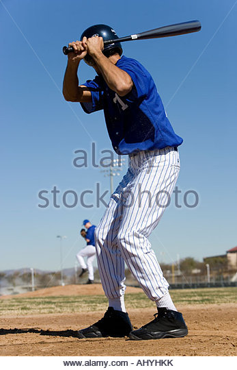 Baseball batter facing pitcher during competitive game, focus on foreground, rear view - Stock Image