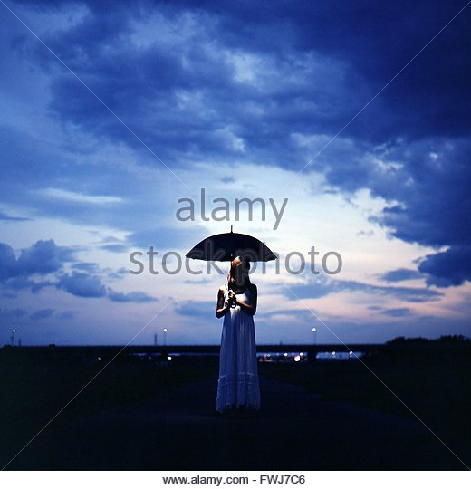 Woman Standing With Umbrella Against Blue Sky - Stock Image