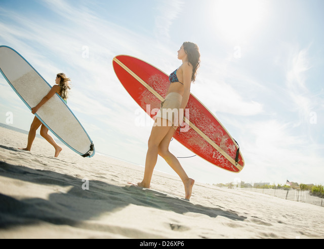 USA, New York State, Rockaway Beach, Two women carrying surfboards on beach - Stock Image
