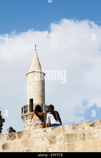 Asian girl tourists sit on the battlements of Larnaca Castle looking up to the minaret of the Djami Kebir Grand - Stock Image