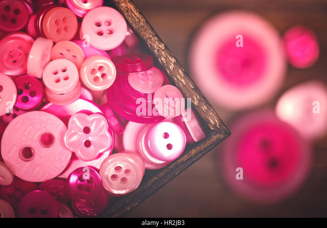 A close up of a box of pink and white buttons, with a nostalgic matte finish - Stock Image