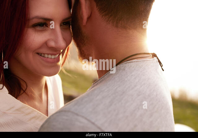 Close up shot of happy young woman embracing her boyfriend and looking away smiling. Loving young couple outdoors. - Stock-Bilder