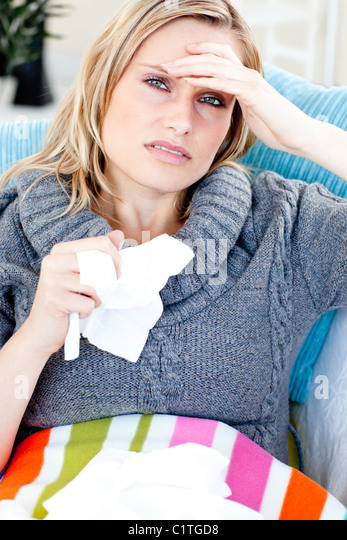 Downcast woman lying on a sofa with tissues and feeling her temperature - Stock Image