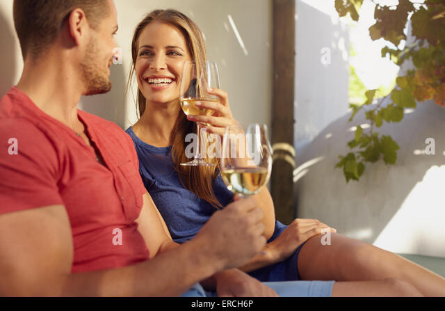 Shot of beautiful young couple enjoying a glass of white wine on an outdoor patio. - Stock-Bilder