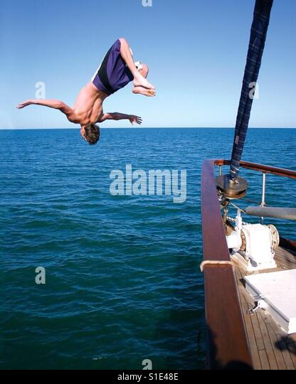 A young man does s backflip off the bow of a yacht into the sea. - Stock-Bilder