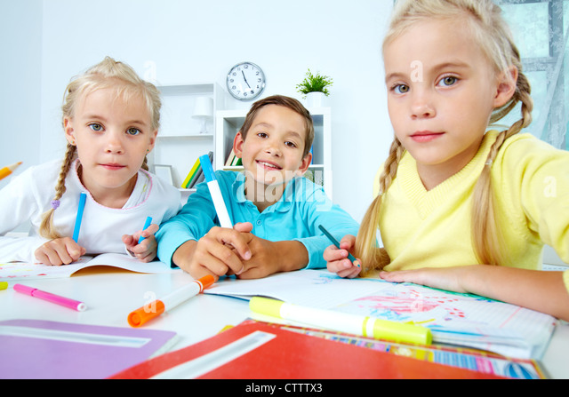 Smart schoolboy and twin girls looking at camera - Stock Image