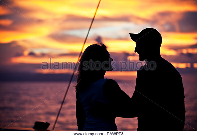 A photographer at sunset, on the western end of Irian Jaya. - Stock Image