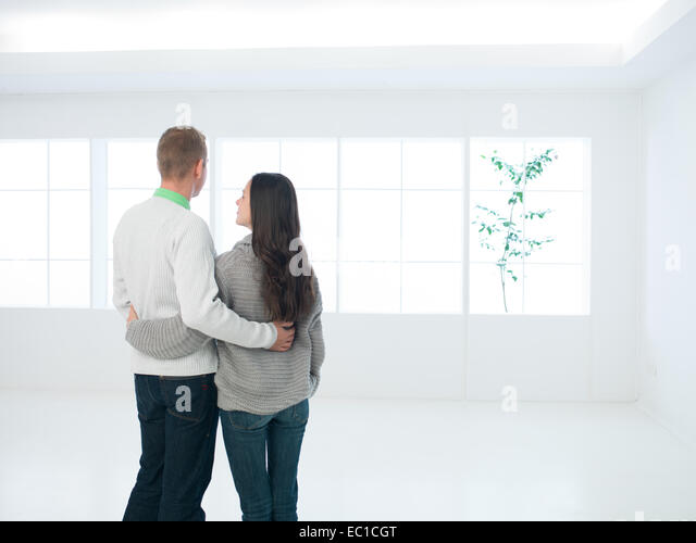 young couple viewing new apartment or house - Stock Image