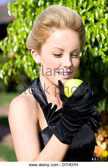 Stunning Beautiful Woman Smiling While Eating Green Apple Directly From A Tree At An Apple Orchid - Stock Image